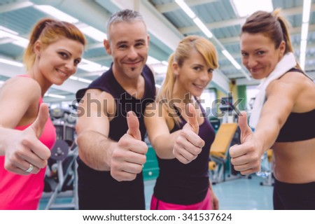 Group of friends with thumbs up smiling on a fitness center after hard training day. Selective focus on hands. - stock photo