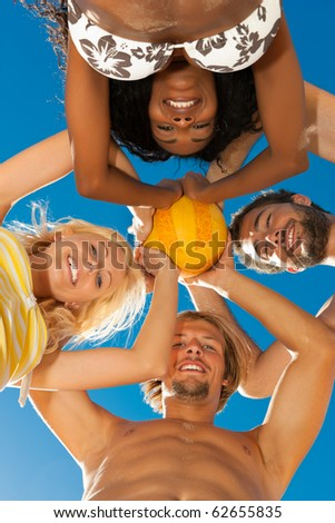 Group of friends - women and men - playing beach volleyball, conceptional shot with all of them looking down with the ball at the camera