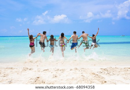 Group of fun-loving young adults playing in the beautiful ocean - stock photo