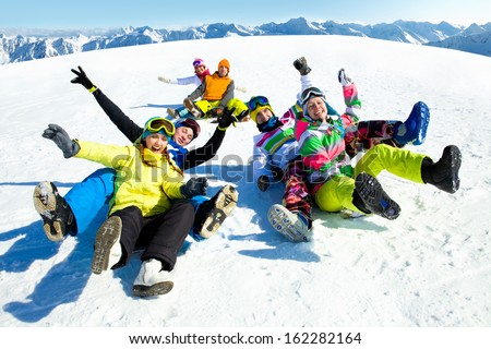 group of funny friends slide downhill together on mountain holiday
