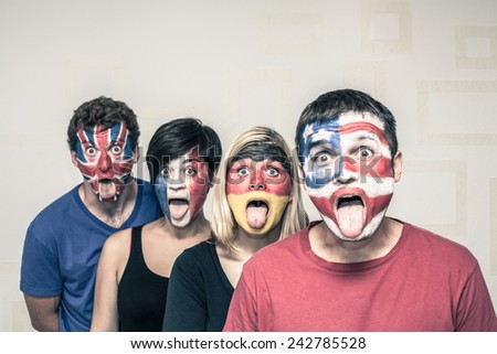 Group of funny people with painted flags on their faces and sticking out tongue.