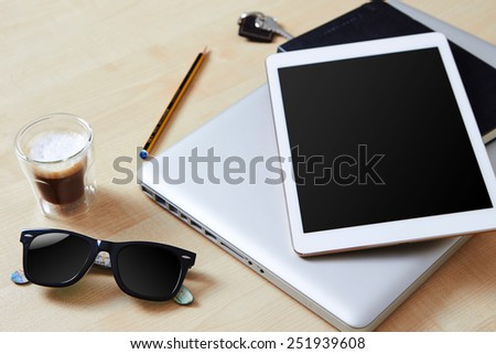 Group of gadgets on a wooden table, digital tablet with blank screen, coffee and sunglasses - stock photo