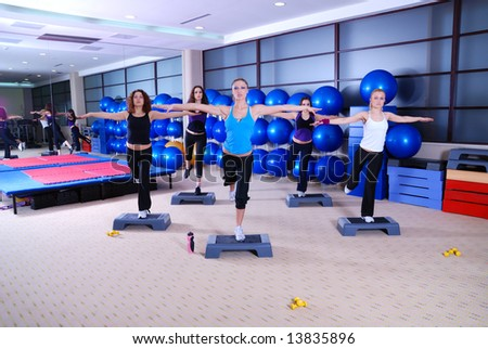 group of girl exercising yoga in fitness club