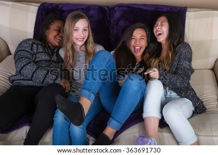 Group of girl friends laughing and having fun at home - stock photo