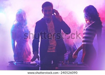 Group of girlfriends dancing in nightclub while dj playing cool music - stock photo