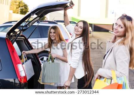 Group of girls after shopping loading a shopping bags in a car trunk - stock photo