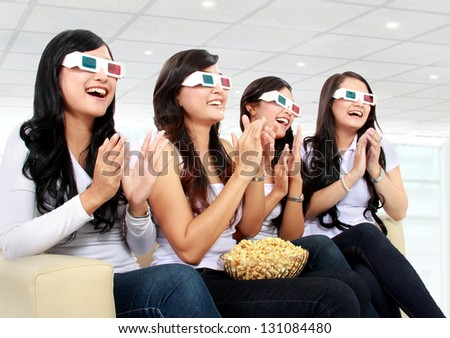 Group of girls clapping watching good 3D movie at home - stock photo