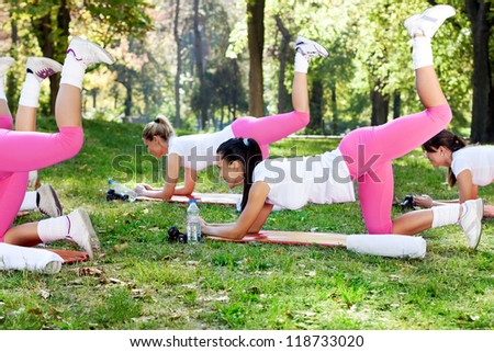 Group of girls doing workout in nature - stock photo
