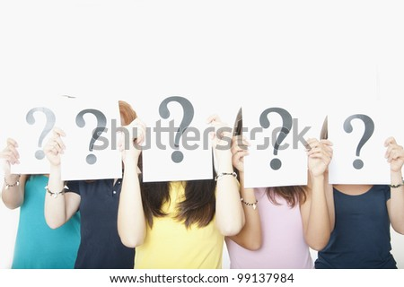 Group of girls holding question mark sign - stock photo