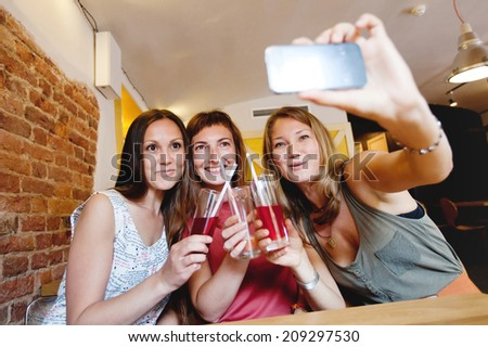 group of girls in cafe doing selfi