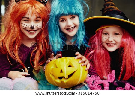 Group of girls in Halloween costumes looking at camera with smiles - stock photo