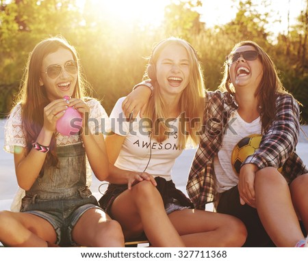 Group of girls laughing while sitting outside enjoying the summer - stock photo