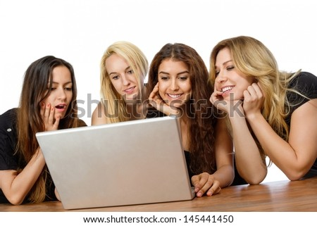 Group of girls looking at a laptop with white background - stock photo