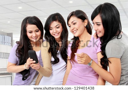 group of girls looking at phone together - stock photo