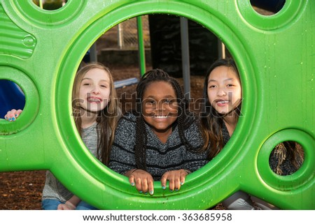 Group of girls playing together at school playground - stock photo