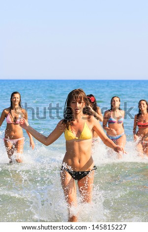 Group of girls running in the sea