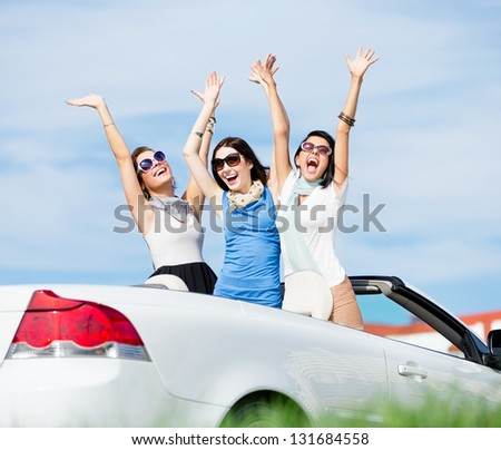 Group of girls stands in the automobile with hands up. Happy journey of joyful teenagers - stock photo