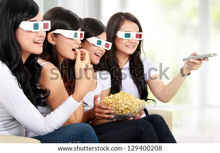 Group of girls watching the movie wear 3D glasses while eating popcorn - stock photo