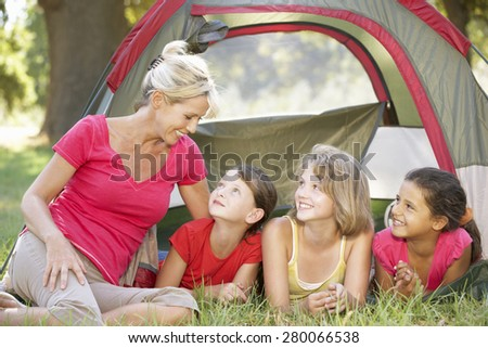 Group Of Girls With Mother Having Fun In Tent In Countryside - stock photo