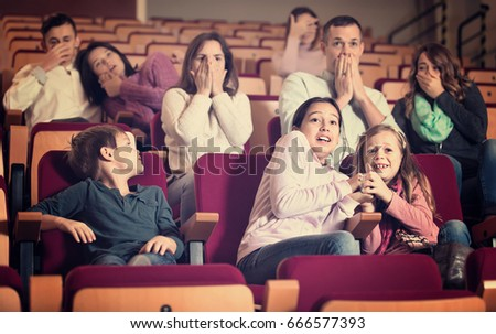 Group of glad cheerful  people watching scary movie in cinema house