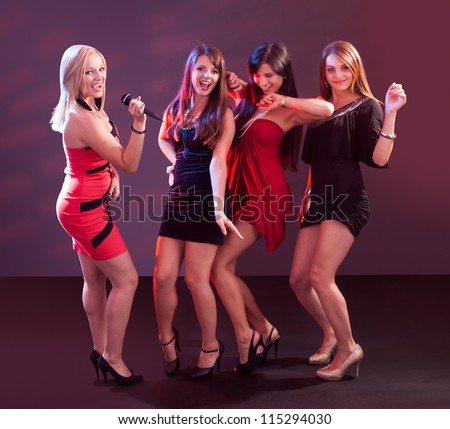 Group of glamorous young women in evening attire dancing together at a nightclub or disco - stock photo