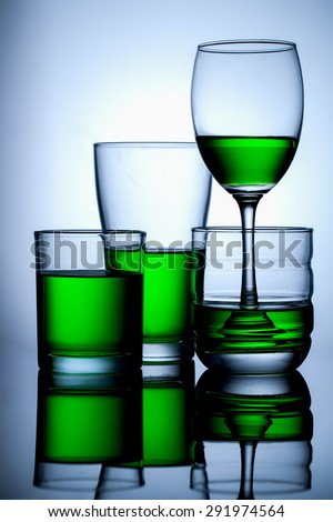 group of glasse whit green water on blue background,and reflex