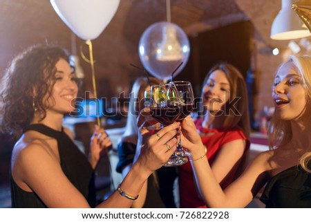 Group of gorgeous Caucasian young girls in elegant dresses smiling drinking wine toasting celebrating birthday in a cafe