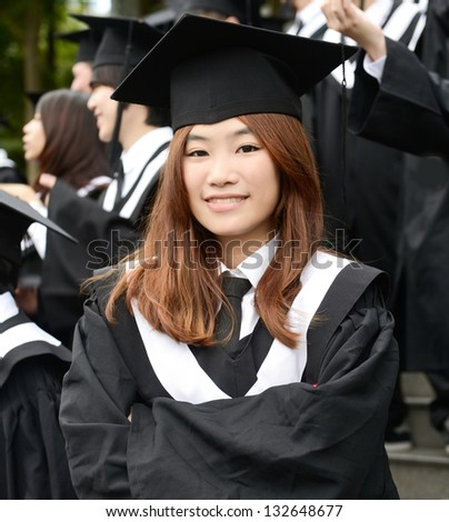 Group of graduate students standing outdoors- female student smiling