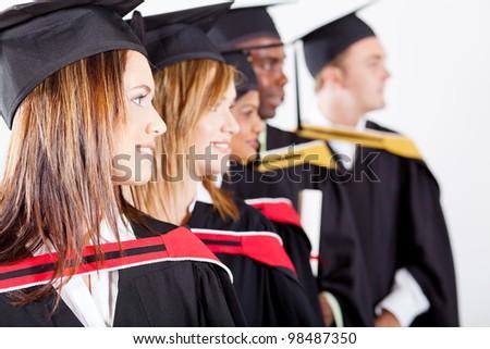 group of graduates looking away at graduation - stock photo