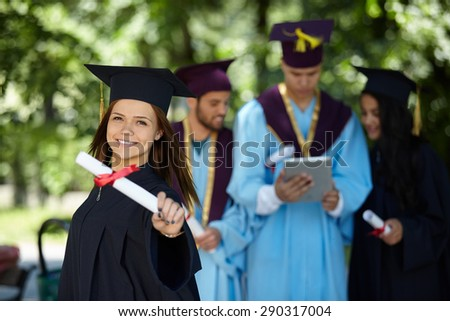 group of graduation students in the park looking happy - stock photo