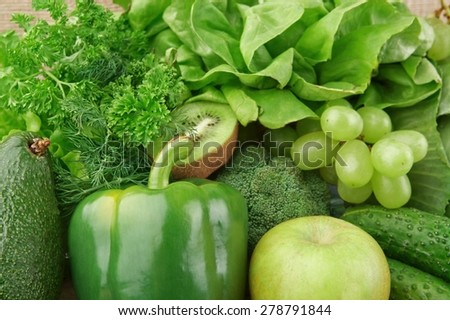 Group of green vegetables and fruits on wooden background