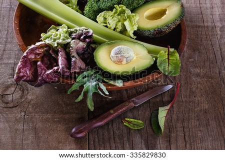 Group of green vegetables on a plate over rustic wooden background - stock photo