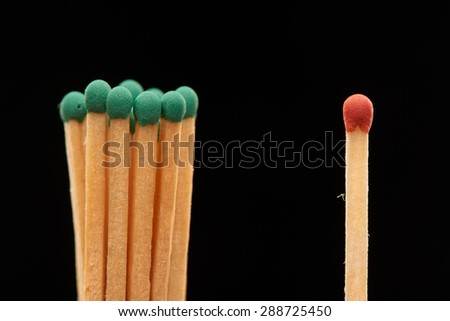 Group of green wooden matches standing with red match, isolated on black background - stock photo