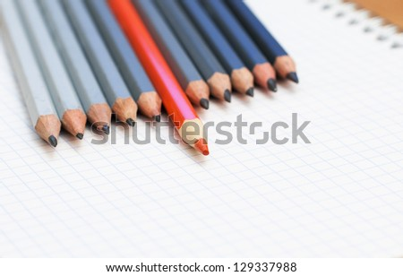 Group of grey wood pencils with one highlighted red as concept for leadership, winning and standing out from the crowd in politics or business. - stock photo