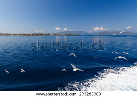 Group of gulls flying towards the island of Aegina, next to ship - stock photo