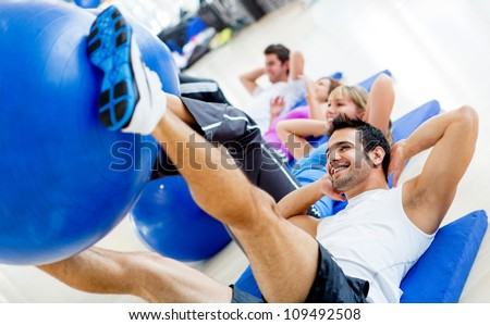 Group of Gym people exercising with Pilates balls