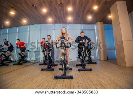Group of gym people on machines, cycling In Class. - stock photo