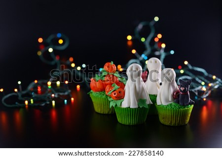 Group of Halloween cupcakes decorated with sugar ghosts and pumpkins. - stock photo