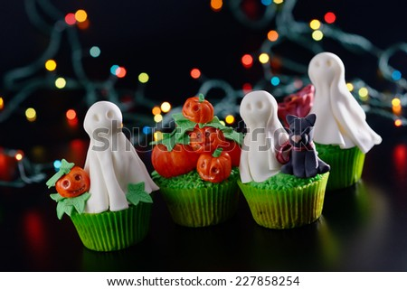 Group of Halloween cupcakes decorated with sugar ghosts and pumpkins. Diagonal framing. - stock photo