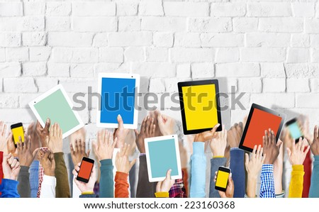 Group of Hands Holding Digital Devices on Brick Wall - stock photo
