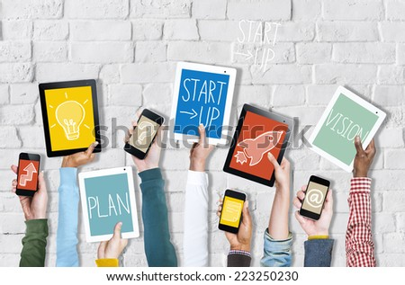 Group of Hands Holding Digital Devices with Startup Concept - stock photo