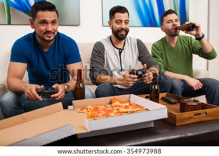 Group of handsome Hispanic young men playing videogames and hanging out at home - stock photo