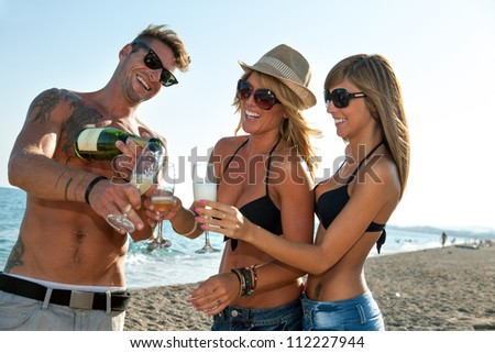 Group of handsome young friends having champagne on beach.