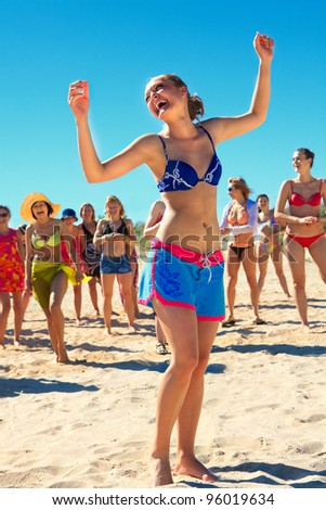 Group of happy active girls dancing at the beach - stock photo