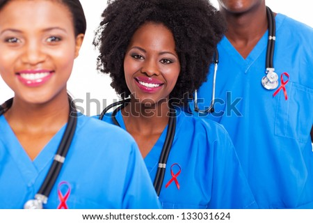 group of happy african healthcare workers with red ribbon for AIDS awareness