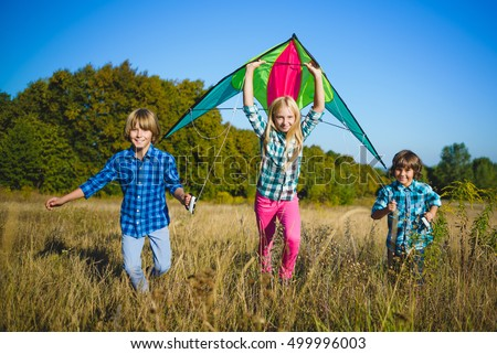 Group of happy and smiling kids playingin with kite outdoor