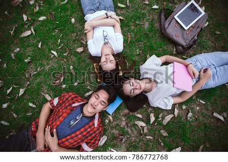 Group of Happy Asian College Students lying and circle heads together on green grass outdoor in garden of university. Relaxing after the tutoring classes.