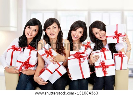 group of happy Beautiful young woman with many gift boxes sitting on the sofa - stock photo