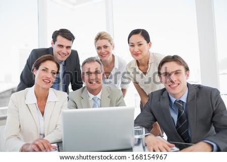 Group of happy business colleagues with laptop at office desk