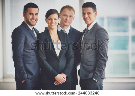 Group of happy business partners looking at camera - stock photo